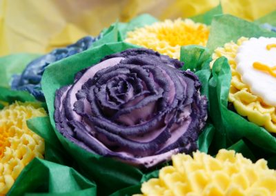 Close Up photo of a purple two tone rose cupcake that's dairy free and egg free, vegan cake